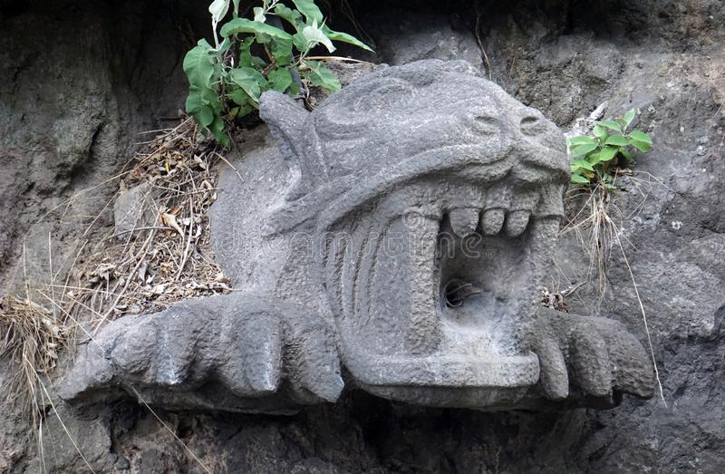 Stone jaguar head front view. Stone jaguar head in pre hispanic architecture kind, feline head carved in a big piece of stone used to drain water from the inner stock images