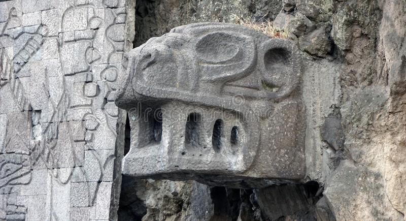 Stone jaguar head. In pre hispanic architecture kind, feline head carved in a big piece of stone used to drain water from the inner flow stock photos