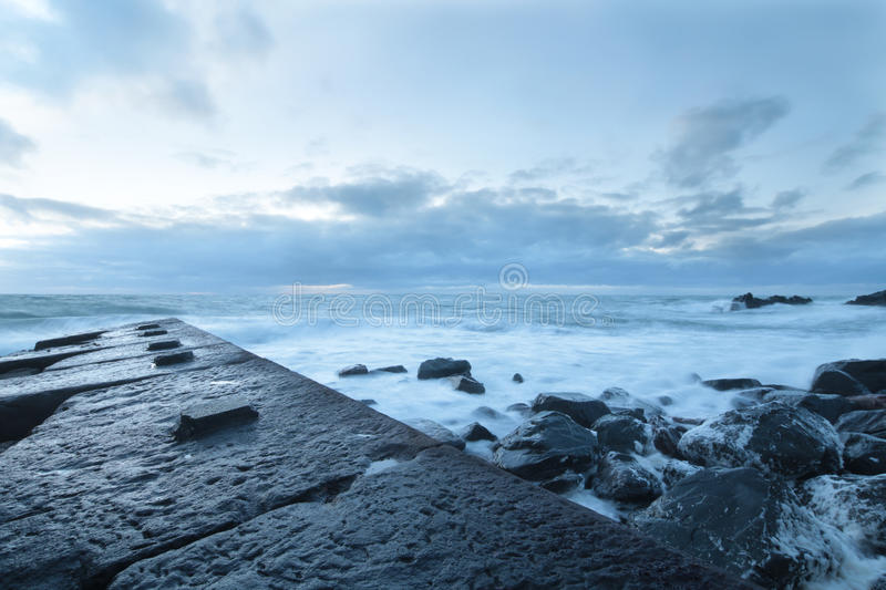 Stone jetty out to sea stock image