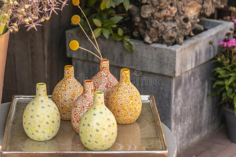 Stone jugs with a motif standing on a golden tray. Stone jugs with a motif placed on a golden tray outdoors stock image
