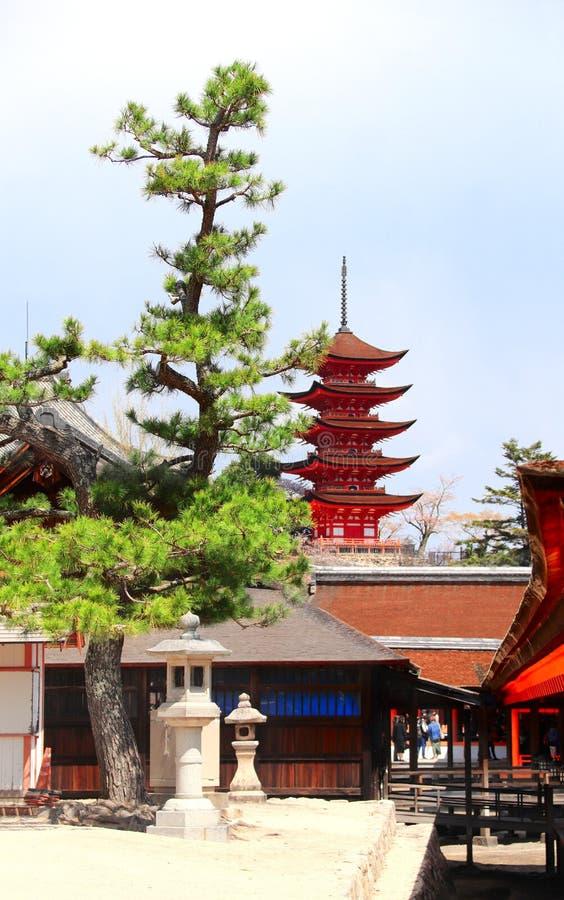 Goju-no-to pagoda of Itsukushima Shrine, Miyajima Island, Japan. Stone lanterns in temple yard and Goju-no-to pagoda Gojunoto pagoda, Five storied pagoda of royalty free stock image