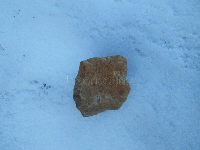 Stone laying on snow royalty free stock photo