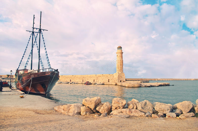 Stone lighthouse and beautiful old ship at sunset stock photo