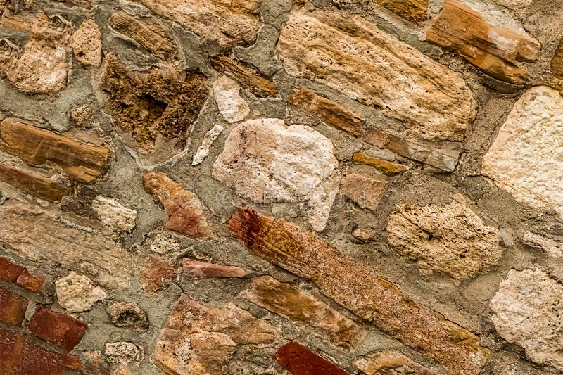 Stone limestone cement wall diagonal blocks beige brown weathered old rough surface texture of the old fence protection decor stock photography