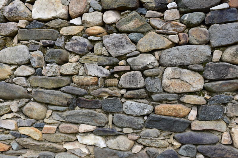 Stone logs for background. Stone Wall of rural Building made with manual work with small pieces of rocks carefully tailored to each other stock images