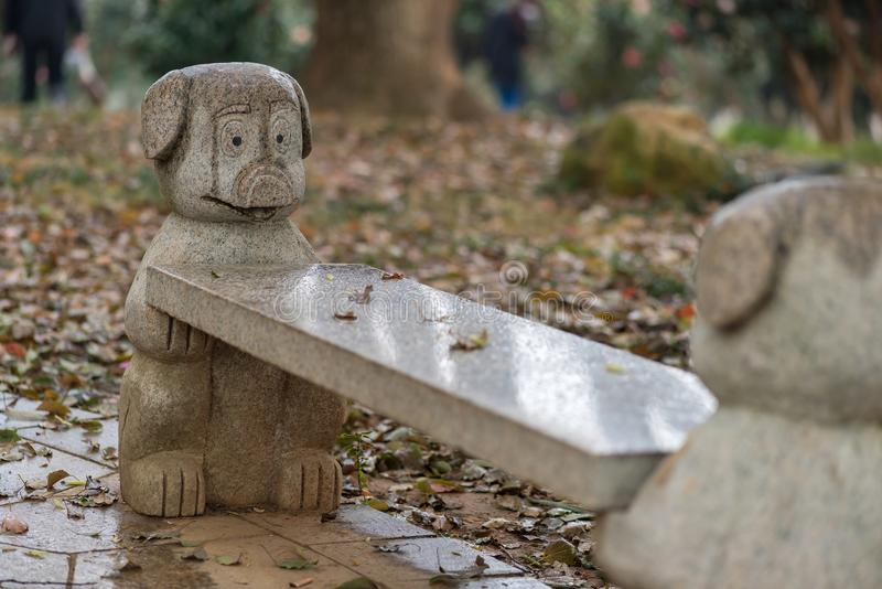 Stone long bench. Cartoon pig image of stone in a corner of the park bench royalty free stock photography