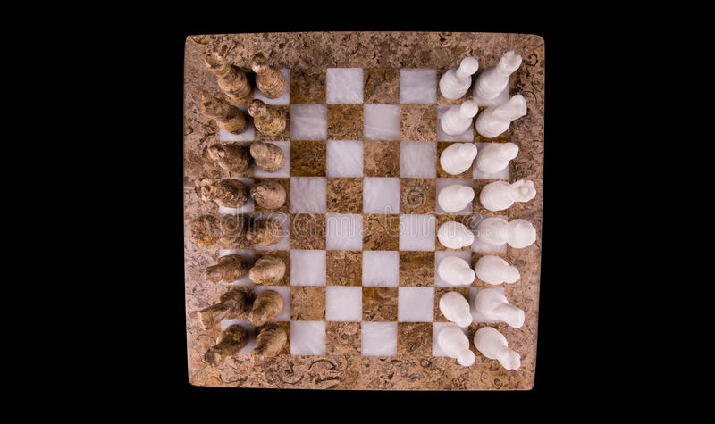 Stone Made Chess Board and Set V. Brown and white pieces of stone made chess set on black background stock photography