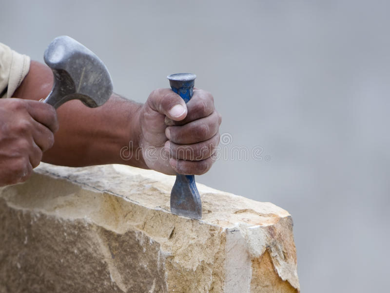 Stone mason chiseling a block of stone. A stone mason holding chisel ready to strike with a hammer to shape a block of stone stock photos