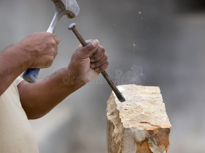 Stone mason shaping block of stone. A stone mason shaping a block of stone with a chisel royalty free stock photos