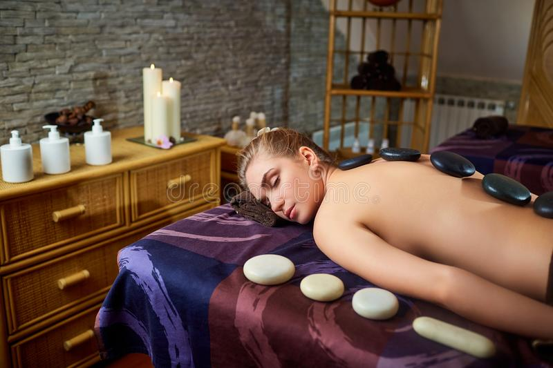 Stone massage back spa for a woman in the beauty center royalty free stock photo