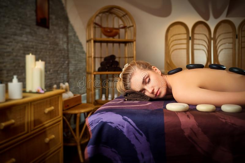 Stone massage back spa for a woman in the beauty center stock photo