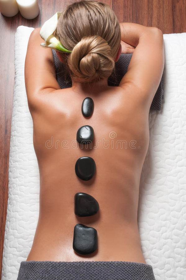 Stone massage. Beautiful woman getting spa hot stones massage in spa salon. royalty free stock images