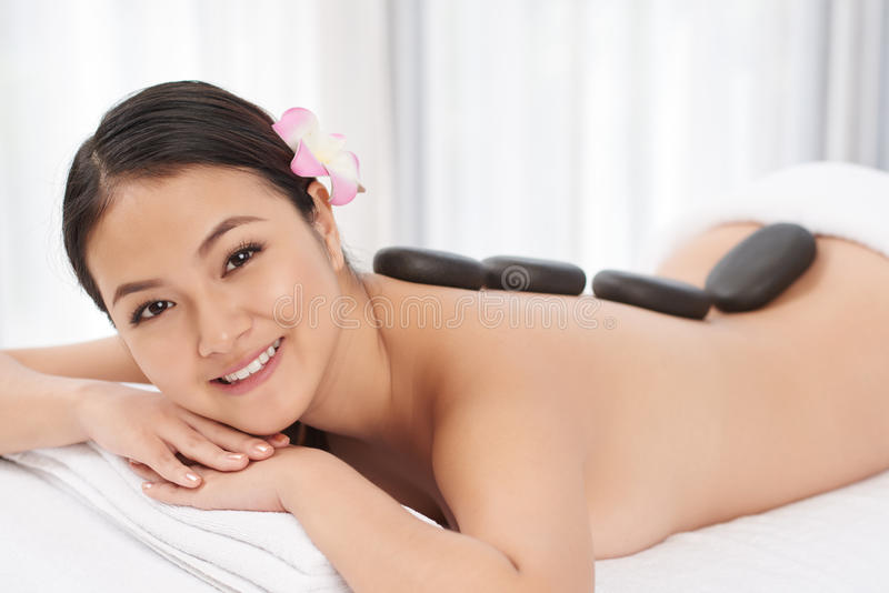 Stone massage. Cheerful Asian woman lying on bed with hot basalt stones on her back stock images