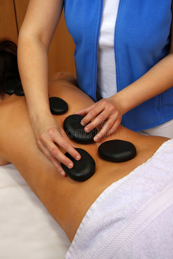 Stone massage in a spa. Hot stone massage in a spa royalty free stock photo