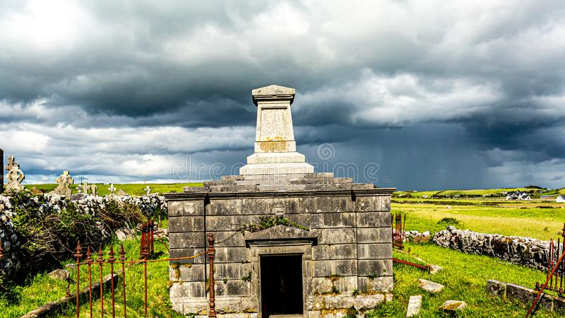 The stone mausoleum of the medieval church of Killilagh in the village of Doolin. Wonderful contrast between sunny and cloudy, with a gray sky and rain in the royalty free stock photography