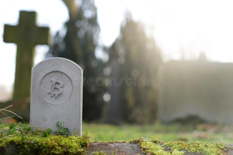 Stone monument/tombstone with bitcoin symbol on cementery - economic/financial concept. Stone monument/tombstone with bitcoin symbol on cementery - sunny blurred royalty free stock image