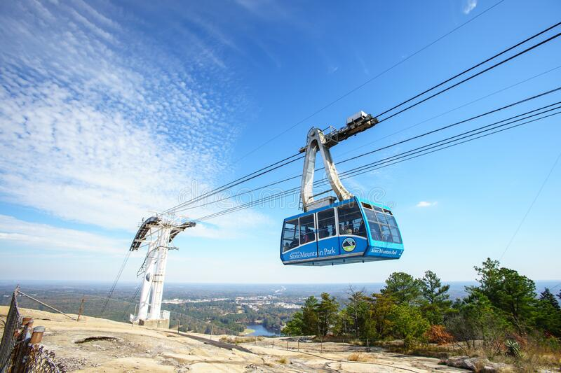 A cable car or gondola passing above stone mountain park. Stone Mountain, Georgia / United States - October 2018 : Skyride, a cable car or gondola riding above royalty free stock photography