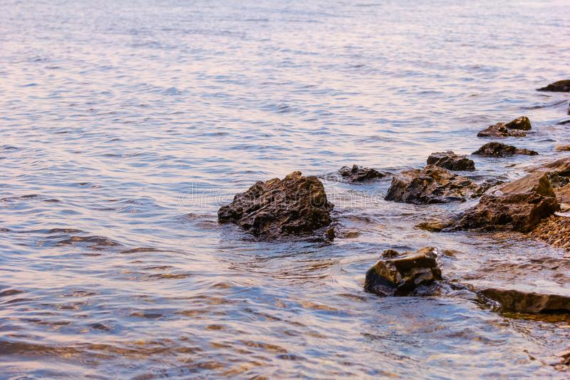 Stone near the river. Waves run on the coastline. Summer sunset. The sun`s rays are reflected in the water.  royalty free stock images