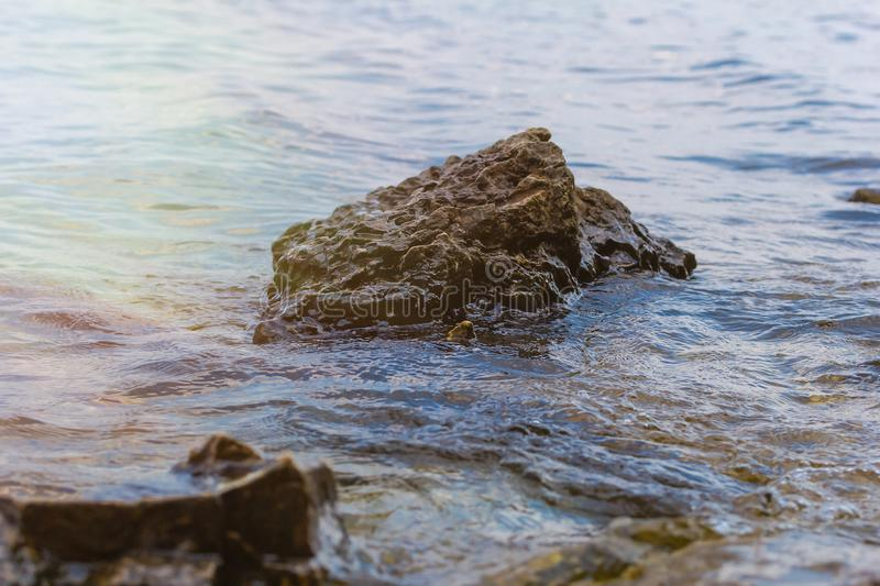 Stone near the river. Waves run on the coastline. Summer sunset. The sun`s rays are reflected in the water.  royalty free stock photo