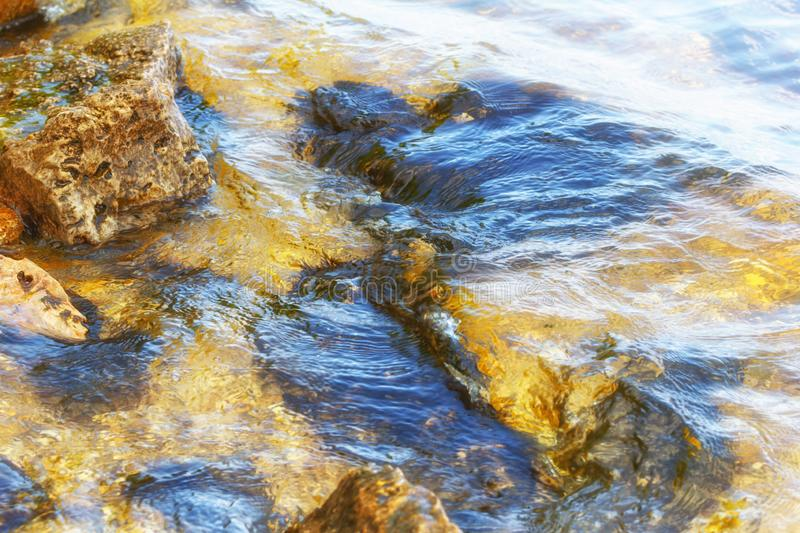 Stone near the river. Waves run on the coastline. Summer sunset. The sun`s rays are reflected in the water.  stock photo