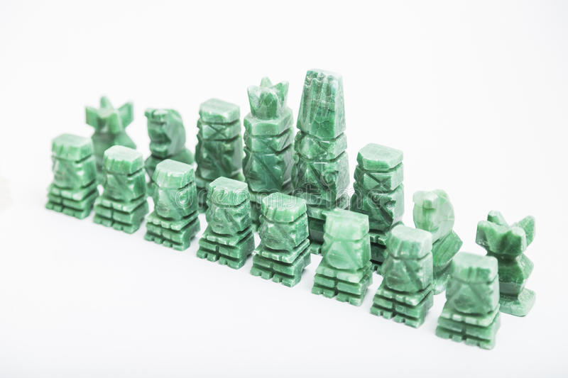 Stone old handmade chess pieces on white background. Shiny green stone vintage old handmade chess pieces on white background stock photography