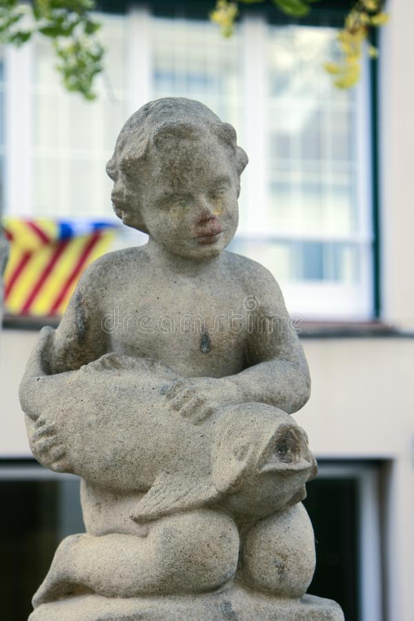 Stone Park sculpture of a little girl with fish. Motaro, Spain royalty free stock image