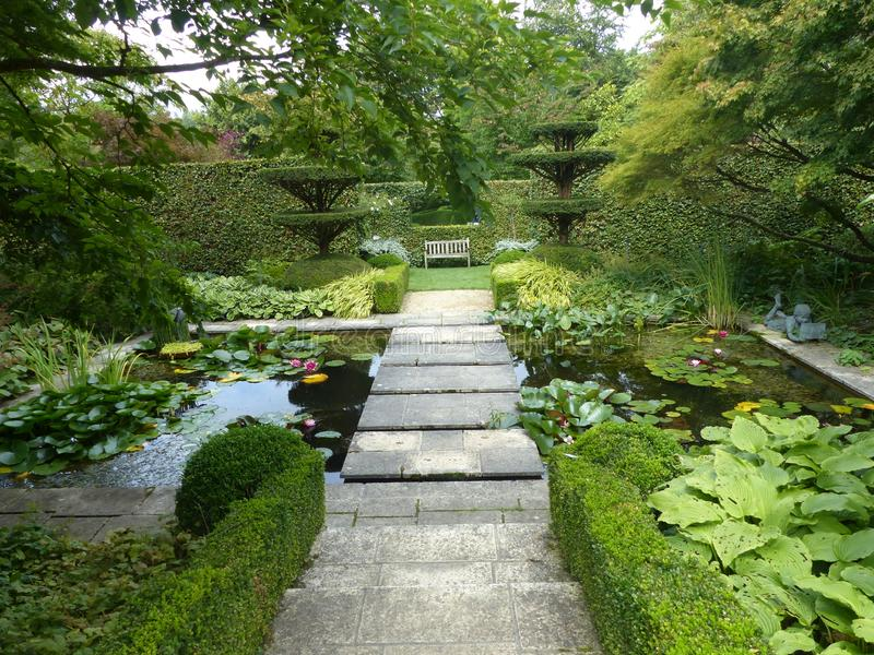 Stone passage crossing two ponds with water lilies in a Castillon garden in France. stock photos