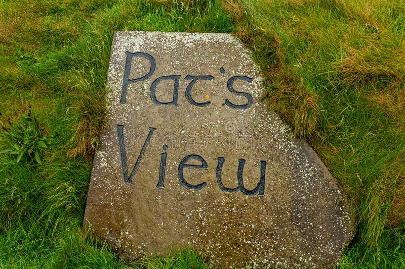 Stone with Pat`s view sign in the coastal walk route from Doolin to the Cliffs of Moher. Geosites and geopark, Wild Atlantic Way, rainy day in county Clare in royalty free stock photo