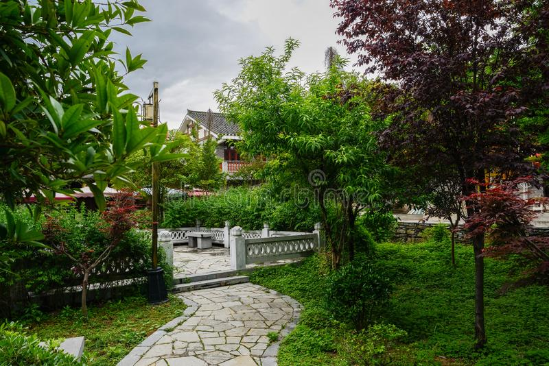 Stone path in garden before tile-roofed buildings on cloudy spring day royalty free stock photography