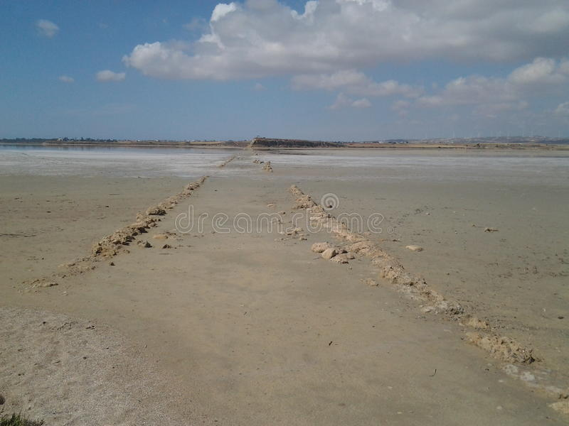 A stone path in the middle of the salt lake beutifull blue sky above stock photography