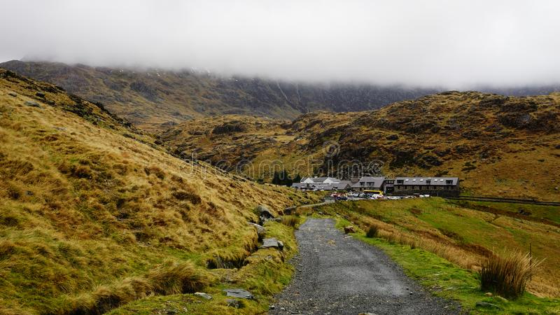 Stone Path with Village Houses in Snowdon, Wales, United Kingdom. Stone path with saturated grass, beautiful mountains, tiny village houses and a foggy sky royalty free stock images