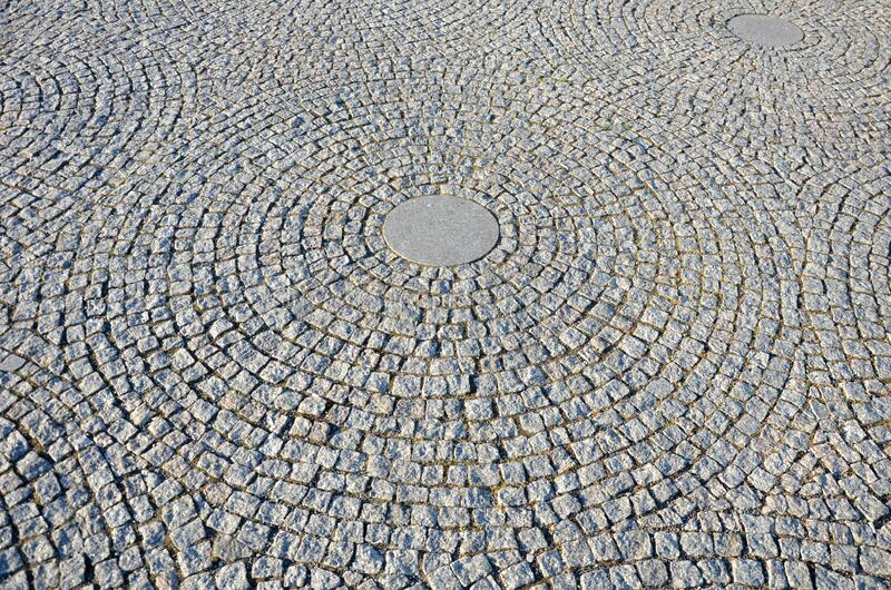Stone paving in the square folded into circles with a larger tile in the middle of gray granite. Stone, pattern, texture, street, pavement, cobblestone, road stock photo