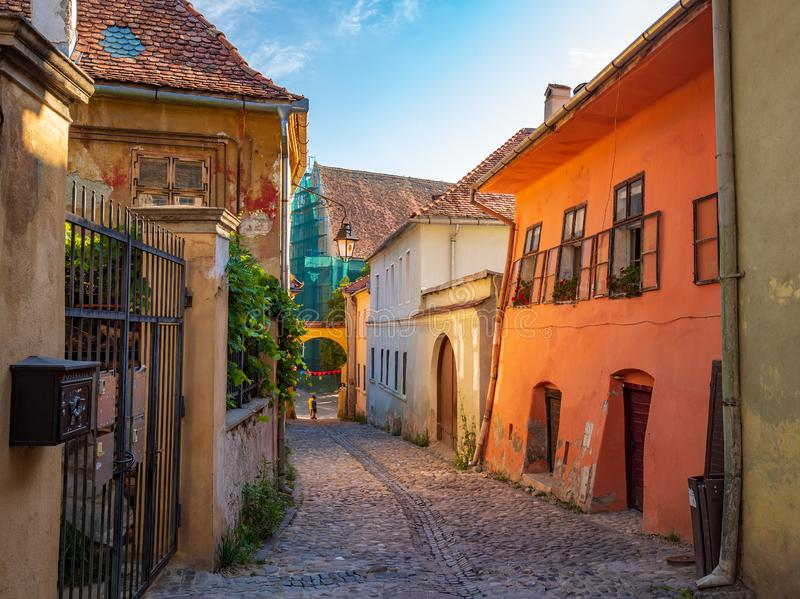 Stone paved medieval streets with colorful houses in Sighisoara, Transylvania region, Romania. Birthplace of Vlad Dracula. UNESCO world heritage site royalty free stock photos