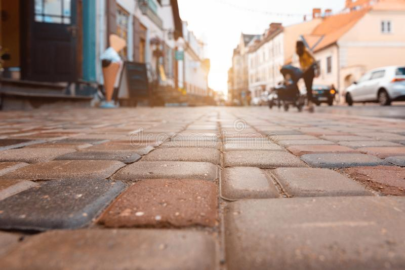 Stone-paved street at sunset in old town of Cesis, Latvia. Mother with a stroller in the background stock photography