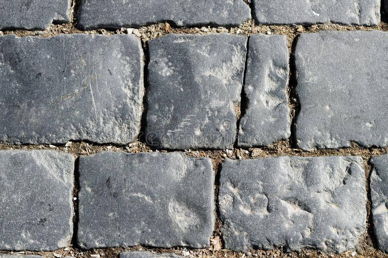 Stone pavement texture, granite cobblestoned pavement background, cobbled stone road regular shapes, abstract background. Of old cobblestone pavement close-up royalty free stock photography