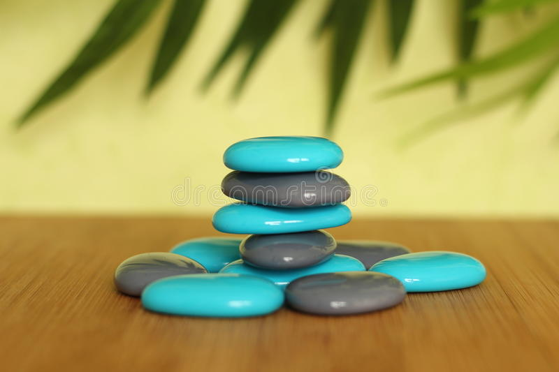 Stone pebble blue and gray posed on a wooden floor and clad in Zen lifestyle on green background royalty free stock photos