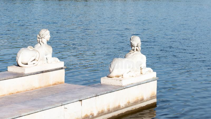 Stone pier with plaster sculptures pond lake. Sphinx sculpture with the body of a lion and the head of a beautiful woman, an royalty free stock image