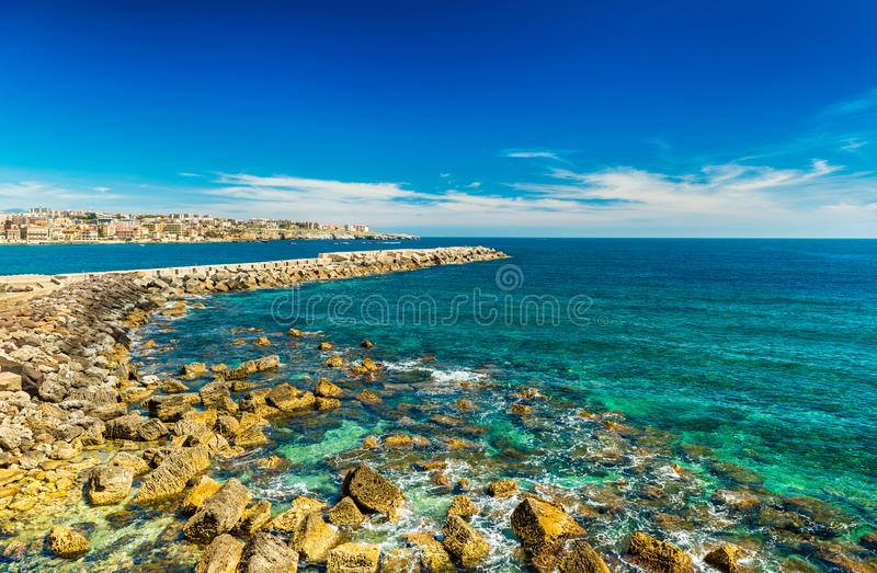 A stone pier in Syracuse, Sicily, Italy. Beautiful seascape with turquoise water and blue sky royalty free stock images