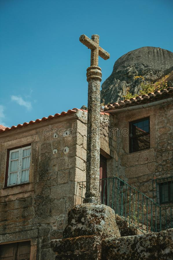 Stone pillory with cross on top in Monsanto. Medieval stone pillory with cross on top, in front of old house on a deserted alley, in a sunny day at Monsanto royalty free stock photos