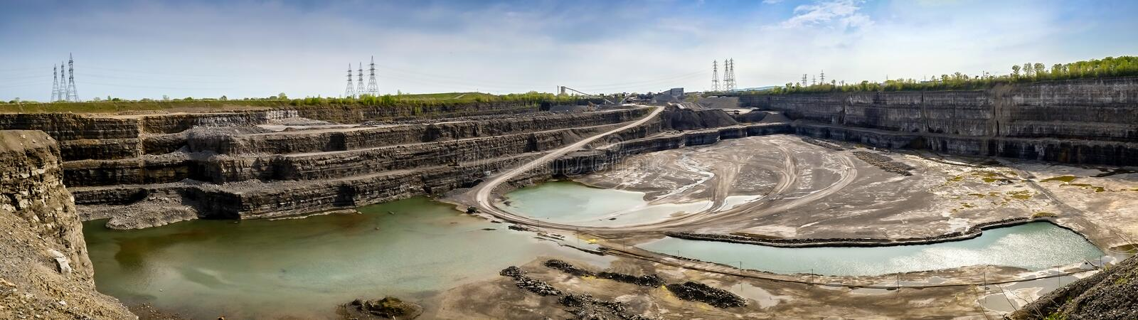 Stone-Pit. Big huge stone pit panorama with power lines in tne back royalty free stock images