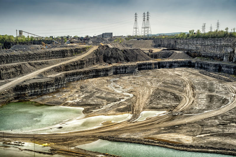 Stone-Pit. Big huge stone pit with power lines in tne back stock image