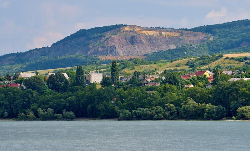 Stone-pit in Hungary. Photographed from Slovakia by the Danube royalty free stock image