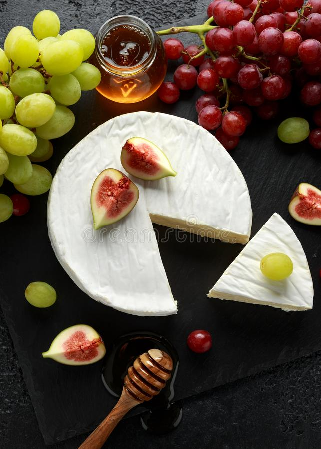 Stone Plate of white cheese brie with figs, green and red grape and honey. Stone Plate of white cheese brie with figs, green and red grape and honey stock photography