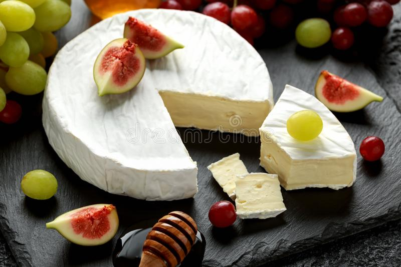 Stone Plate of white cheese brie with figs, green and red grape and honey. Stone Plate of white cheese brie with figs, green and red grape and honey stock photo