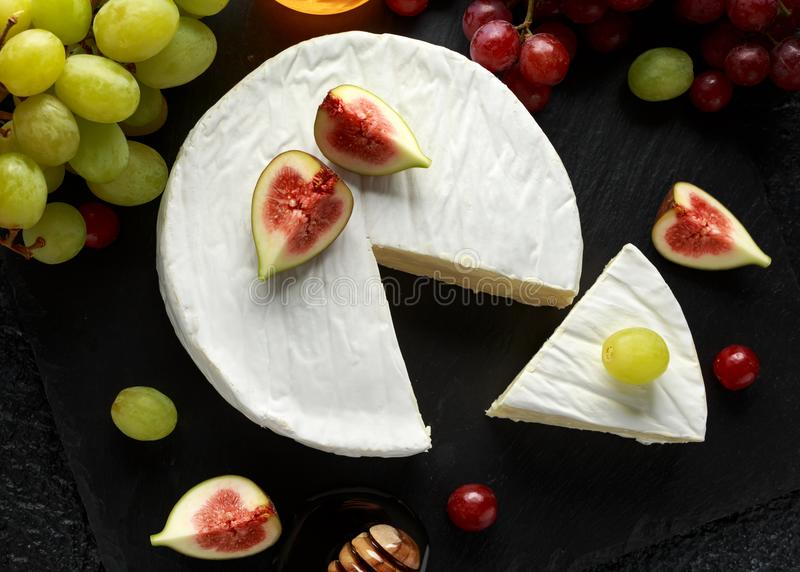 Stone Plate of white cheese brie with figs, green and red grape and honey. Stone Plate of white cheese brie with figs, green and red grape and honey royalty free stock images