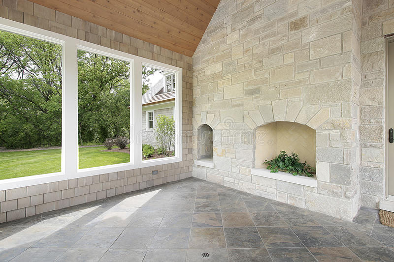 Stone porch with fireplace. Stone porch in new construction home with fireplace stock image