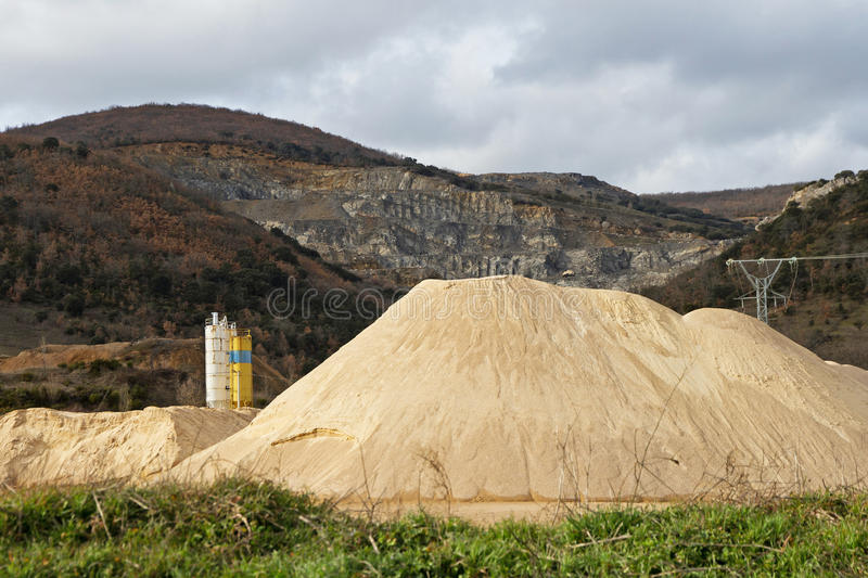 Stone Quarry and Sand Mountain, in gravel pit. Pierced mountain quarry for stone quarrying and sand. Sand Mountain gravel pit in the foreground in silos and royalty free stock photo