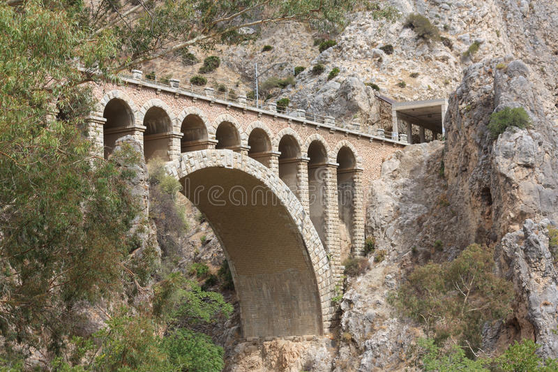 Stone railway bridge. In mountainous terrain, leading into a tunnel stock photo