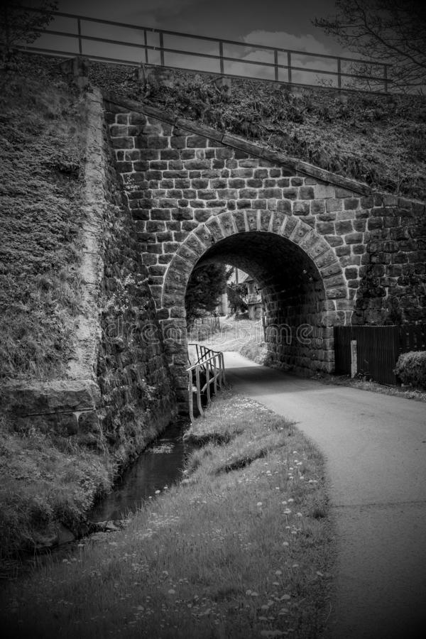 Stone railway viaduct that crosses the road and river royalty free stock image