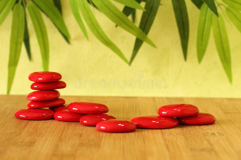 Stone red pebble laid on a wooden floor and stacked on several columns in zen lifestyle on green background. Stone red pebble laid on a wooden floor and stacked stock photos